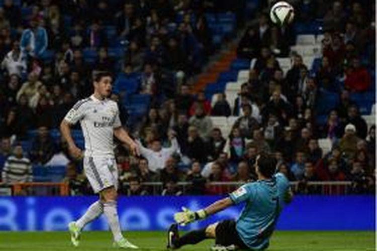 Gelandang Real Madrid, James Rodriguez (kiri), melakukan chip untuk mencetak gol ke gawang Cornella dalam babak 32 besar Copa del Rey di Santiago Bernabeu, Selasa (2/12/2014).