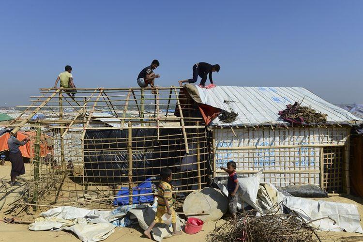 Para pengungsi Rohingya bekerja sama mendirikan tenda penampungan di kamp pengungsi di Kutupalong, distrik Ukhia, Bangladesh.