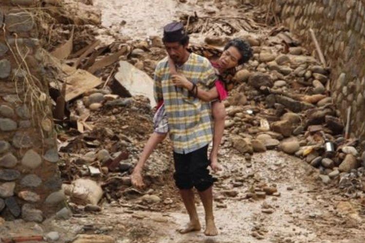 Seorang pria menggendong istrinya yang sedang sakit di tengah kondisi bencana di Desa Sukarame, Kecamatan Sajira, Kabupaten Lebak.