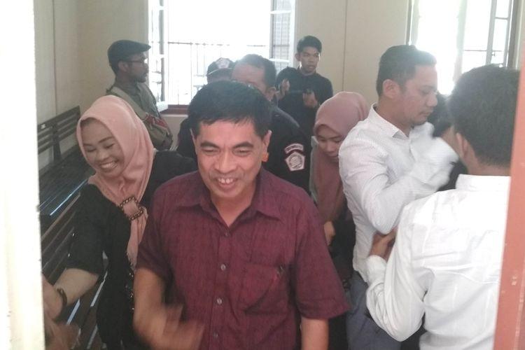 Sekretaris KPU Kota Makassar Sabri (merah) saat tersenyum usai mendengarkan dakwaan jaksa penuntut umum dalam kasus dugaan korupsi dana hibah Pilwalkot Makassar di Pengadilan Negeri Makassar, Kamis (19/9/2019).