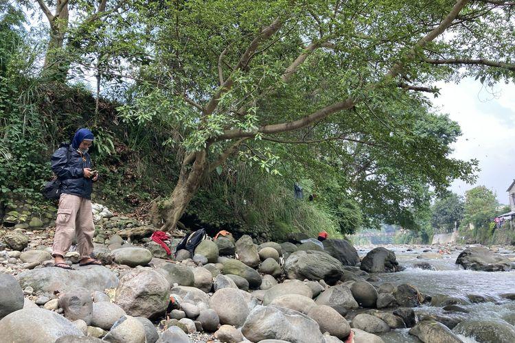 Seorang wisatawan sedang berdiri di salah satu titik di tepian Sungai Ciliwung yang memiliki pesona indah, meski di beberapa area terlihat banyak tumpukan sampah plastik, Kota Bogor, Senin (24/5/2021).