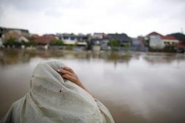 Warga menyaksikan luapan Kali Ciliwung di Bukit Duri, Tebet, Jakarta Selatan, Kamis (23/1/2014). Luapan Kali Ciliwung sejak Selasa, 21 Januari lalu menyebabkan rumah dari 116.382 jiwa terendam dan 79.614 jiwa mengungsi. KOMPAS/AGUS SUSANTO