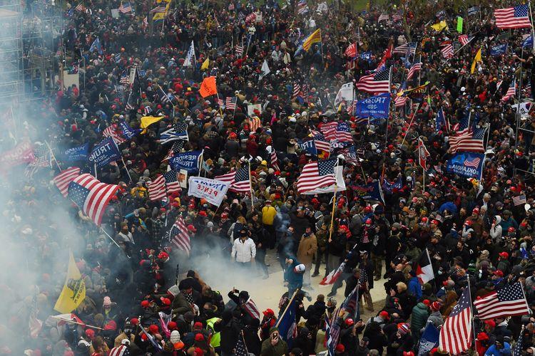 Massa pendukung Presiden Amerika Serikat (AS) Donald Trump bentrok dengan pasukan keamanan saat mereka menerobos masuk ke Gedung Capitol, Washington DC, pada 6 Januari 2021.