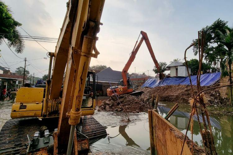 Kementerian PUPR menurunkan sejumlah alat berat untuk mengeruk timbunan material longsoran dari tebing Kali Ciputat akibat hujan deras yang mengguyur wilayah Tangerang Selatan, Jumat (11/06/2021).