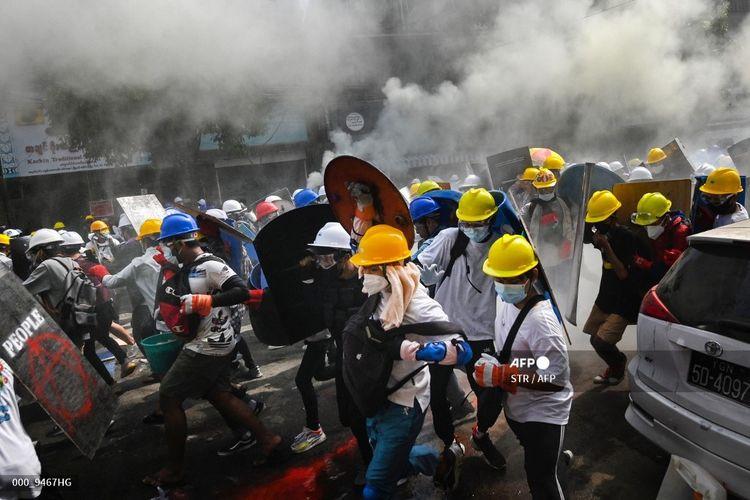 Para pengunjuk rasa memegang perisai buatan sendiri saat mereka berlari selama demonstrasi menentang kudeta militer di Yangon pada Tabu (3/3/2021).