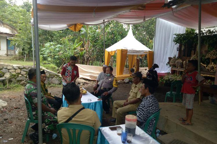 Polisi saat memberikan penjelasan larangan mengadakan kegiatan pada warga Jember yang menggelar resepsi pernikahan