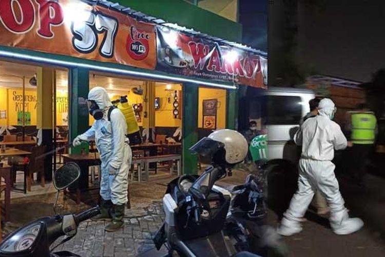 Anggota Tim Kimia Biologi Radioaktif (KBR) Gegana Brimob Polda Jatim menyemprotkan cairan disinfektan ke sebuah warkop berlokasi di Jalan Raya Gunungsari I, Wonokromo, Surabaya.
