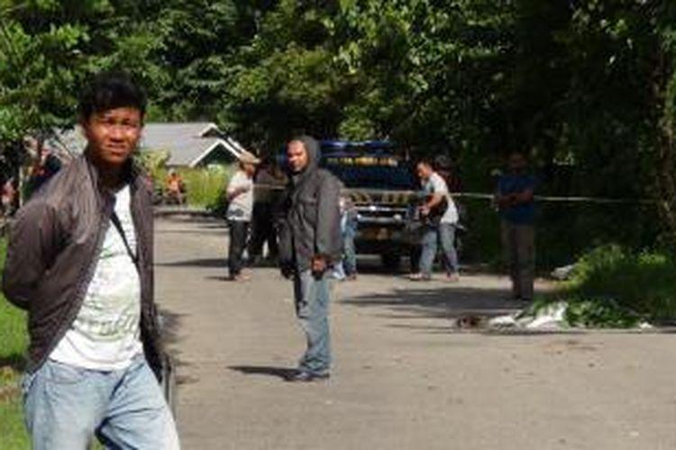 Sejumlah aparat kepolisian dari Polsek Mimika Baru dan Polres Mimika mengamankan lokasi penemuan mayat Din Murib, warga Kampung Landu Mekar Kwamki Narama yang menjadi korban pengeroyokan berujung kematian di Jalan Sosial, Gorong-Gorong, ujung Bandara Mozes Kilangin Timika, Senin (9/6/2014).