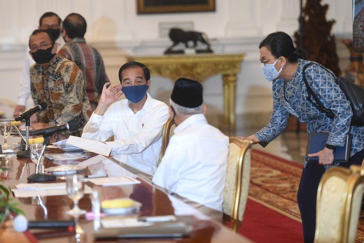 Presiden Joko Widodo (tengah, bermasker biru) didampingi Wakil Presiden Maruf Amin (membelakangi kamera) berbincang dengan Menteri Keuangan Sri Mulyani (kanan) sebelum memimpin rapat terbatas (ratas) mengenai percepatan eliminasi Tuberkulosis (TBC) di Istana Merdeka, Jakarta, Selasa (21/7/2020).