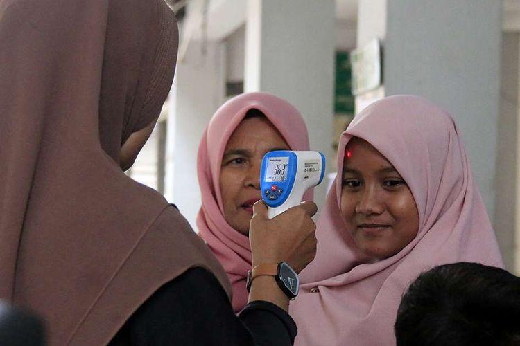 Pemindaian suhu tubuh pada calon penumpang kapal menggunakan alat yang disediakan oleh Kantor Kesehatan Pelabuhan Kelas Banda Aceh, di Pelabuhan Ulee Lheu, Banda Aceh, Kamis (12/3/2020). KKP Ulee Lheu Banda Aceh menyediakan dua unit alat pengecek suhu tubuh (infrared thermometer) dan cairan antiseptik di pelabuhan itu guna pencegahan dari penyebaran virus corona (Covid-19).