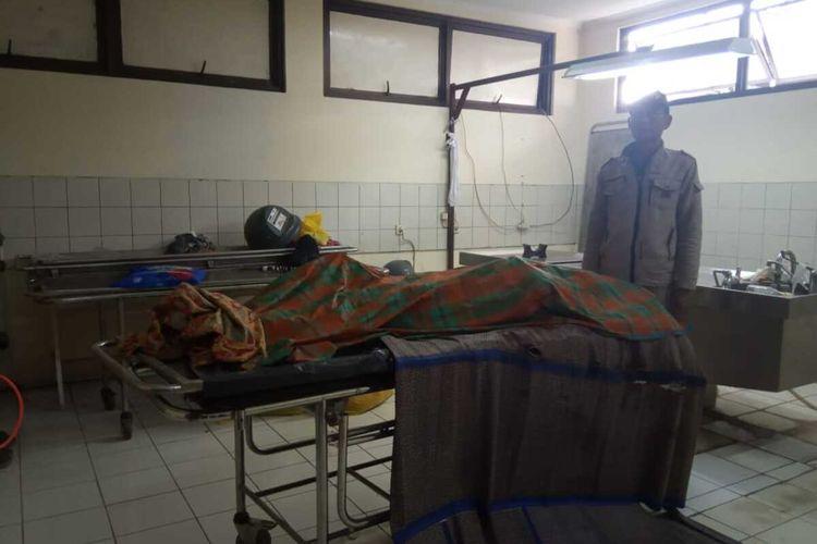 Roji (49) berdiri disamping jenazah Oon di kamar mayat ruang RSUD Karawang, Rabu (5/2/2020).