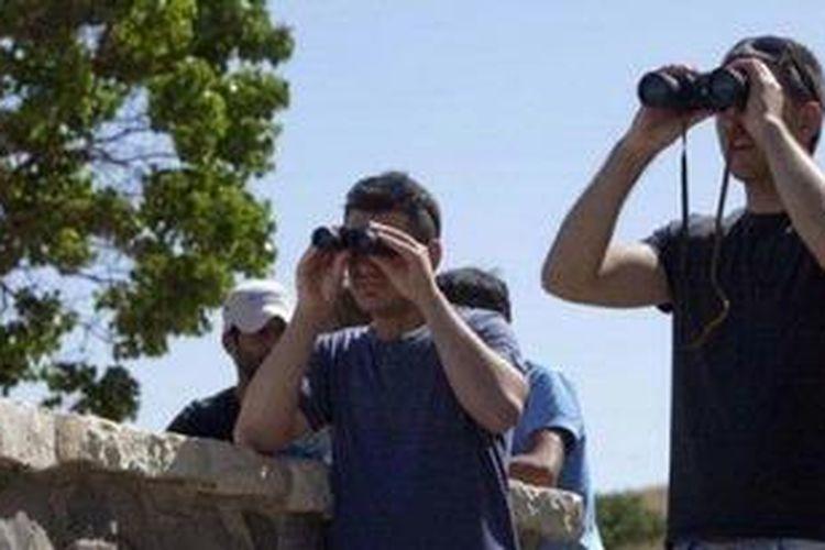 Warga Israel yang tinggal di dekat perbatasan dengan Suriah di dataran tinggi Golan menggunakan teropong menyaksikan jalannya pertempuran antara pasukan pemerintah dan pemberontak Suriah memperebutkan perbatasan Quneitra, Kamis (6/6/2013).