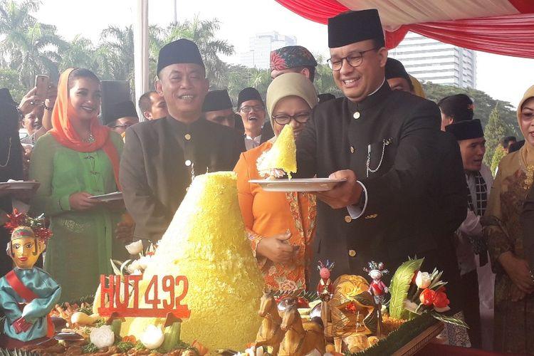 Gubernur DKI Jakarta Anies Baswedan memotong tumpeng selepas upacara HUT ke-492 Jakarta di Monas, Sabtu (22/6/2019).