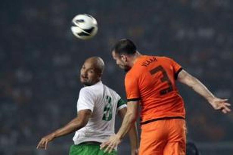 Pemain Timnas Indonesia, Sergio van Dijk melakukan duel udara dengan pemain Timnas Belanda, Ron Vlaar pada laga ujicoba di Stadion Utma Gelora Bung Karno, Jakarta Selatan, Jumat (7/6/2013) malam. Skor sementara Indonesia kalah 0-2.