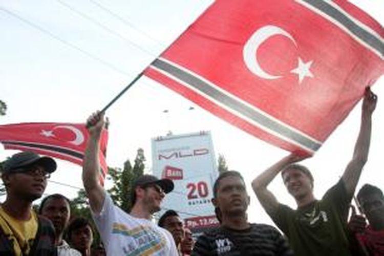 Dua turis asing mengibarkan bendera Aceh yang diambil dari massa yang melakukan aksi di Simpang Kodim, Banda Aceh, Kamis (4/4/2013). Kunjungan Mendagri Gamawan Fauzi ke Banda Aceh dimanfaatkan warga untuk mendukung bendera Aceh bergambar Bulan Bintang.