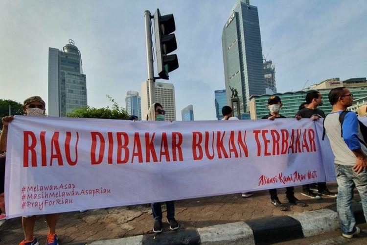 Warga Riau yang tergabung dalam Persatuan Masyarakat Riau Jakarta (PMRJ) gelar aksi pakai masker di Car Free Day (CFD), Jalan Jenderal Sudirman, Jakarta Pusat, sebagai bentuk kepedulian bencana kabut asap di Provinisi Riau, Minggu (15/9/2019).