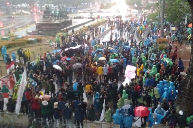 Mahasiswa tetap menggenggam aksi di tengah hujan deras di kawasan Patung Kuda Jakarta Pusat, Jumat (16/10/2020)