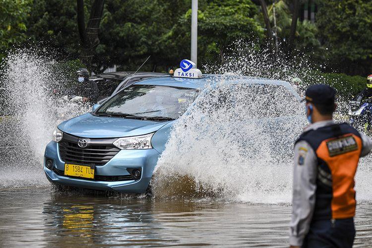 Sebuah mobil taksi memacu kecepatan saat melintasi banjir di kawasan Jalan Jenderal Sudirman, Jakarta, Sabtu (20/2/2021). Intensitas hujan yang tinggi serta buruknya drainase menyebabkan banjir di sejumlah wilayah Ibu Kota.