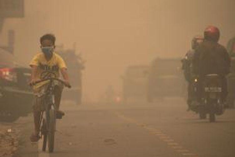 Seorang anak bersepeda dengan menggunakan masker di Kota Pekanbaru, Riau, Kamis (13/3/2014). Kabut asap yang disebabkan kebakaran lahan dan hutan tersebut semakin pekat. Pemerintah Provinsi Riau mengimbau warga untuk menggunakan masker terkait kualitas udara yang memburuk.
