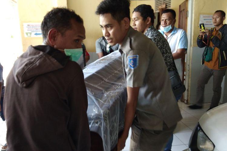 Sejumlah kerabat, petugas dari BP3TKI, pengurus Rumah Pengharapan Gereja Masehi Injili di Timor (GMIT) dan Anggota DPRD Kabupaten TTS, menggotong jenazah Nikolaus Banunaek dari kamar jenazah RSU WZ Johannes, menuju mobil jenazah, Senin (19/3/2018).