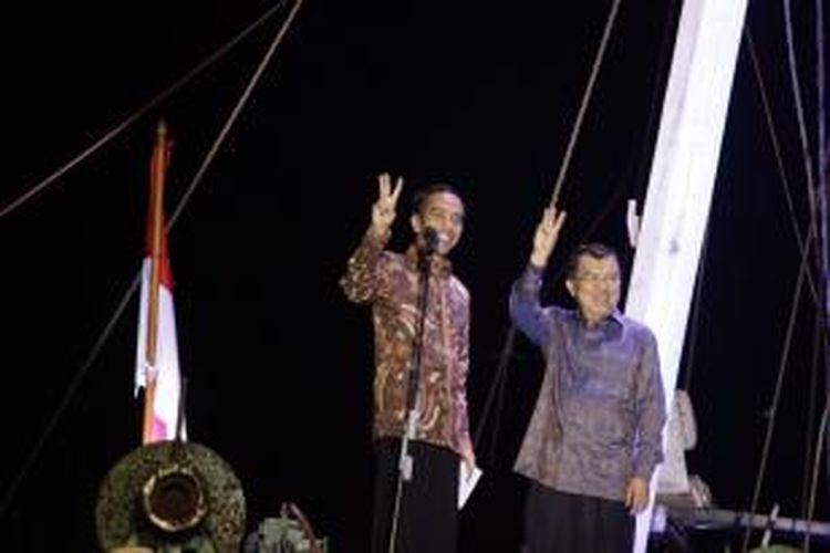 Pasangan Presiden dan Wakil Presiden terpilih, Joko Widodo-Jusuf Kalla melambaikan salam tiga jari seusai memberikan pidato kemenangan, di atas sebuah kapal pinisi di Pelabuhan Sunda Kelapa, Jakarta Utara, Selasa (22/7/2014). Berdasarkan rekapitulasi suara yang dihitung oleh Komisi Pemilihan Umum, Joko Widodo-Jusuf Kalla unggul atas pasangan Prabowo Subianto-Hatta Rajasa.