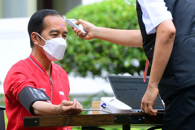Petugas mengecek suhu tubuh Presiden Joko Widodo (kiri) sebelum disuntik dosis kedua vaksin Covid-19 produksi Sinovac di halaman tengah Istana Merdeka, Jakarta, Rabu (27/1/2021). Penyuntikan dosis kedua vaksin Covid-19 ke Presiden Joko Widodo tersebut sebagai lanjutan vaksinasi tahap pertama 13 Januari 2021 .