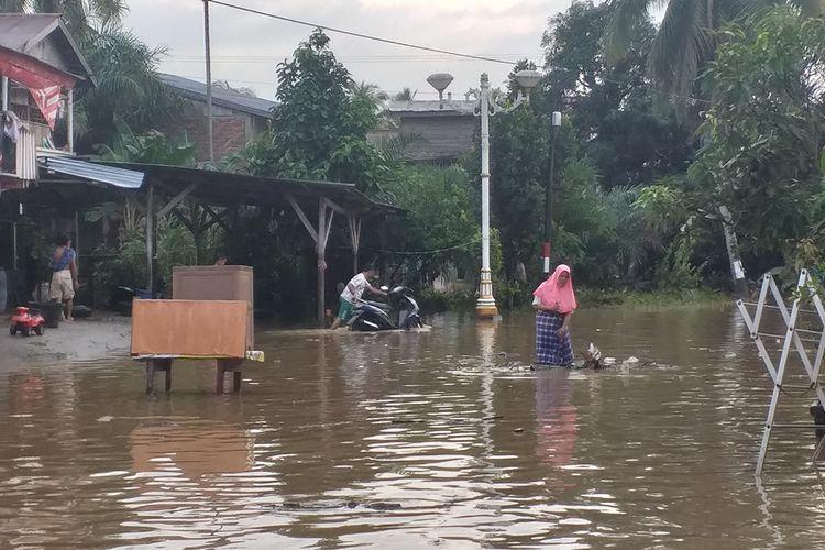 Warga membuang sampah yang menumpuk di rumahnya akibat banjir di Desa Babussalam, Kecamatan Rambah, Kabupaten Rohul, Riau, Rabu (27/11/2019).