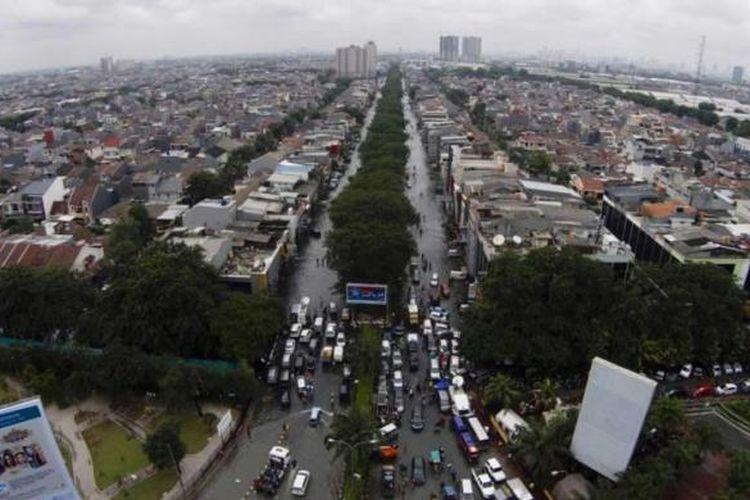 Banjir menggenangi kawasan permukiman dan perekonomian di Kelapa Gading, Jakarta Utara, Selasa (10/2/2015). Jakarta menghadapi masalah penurunan muka tanah. Kondisi itu diperparah oleh semakin minimnya daerah resapan air yang diganti dengan hunian dan gedung-gedung pencakar langit.