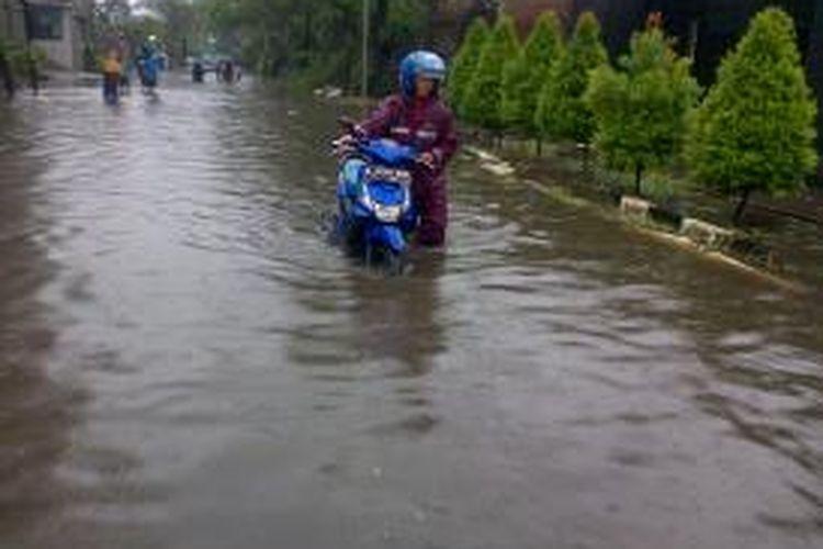 Salah satu pengendara terpaksa menuntun motornya lantaran banjir yang menggenangi jalan Peternakan II, Kapuk, Jakarta Barat, Senin (9/2/2015)