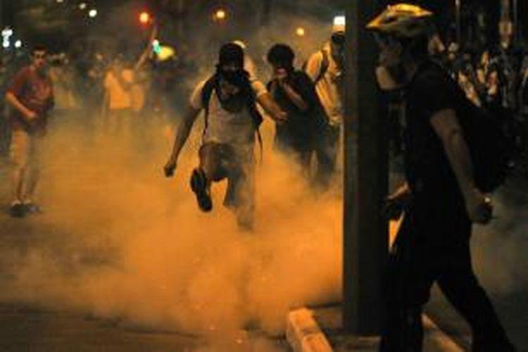 Demonstran menendang peluru gas air mata saat bentrokan dengan polisi di luar Stadion Mineirao di Belo Horizonte, Brazil, 26 Juni 2013, saat Brazil dan Uruguay sedang bertanding salam semifinal Piala Konfederasi Brazil 2013.