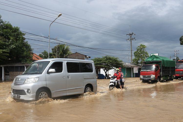 Banjir akibat jebolnya tanggul 2 sungai menggenangi jalan raya Jombang - Madiun, di Desa Gondangmanis, Kecamatan Bandar Kedungmulyo, Kabupaten Jombang, Jawa Timur, Kamis (4/2/2021).