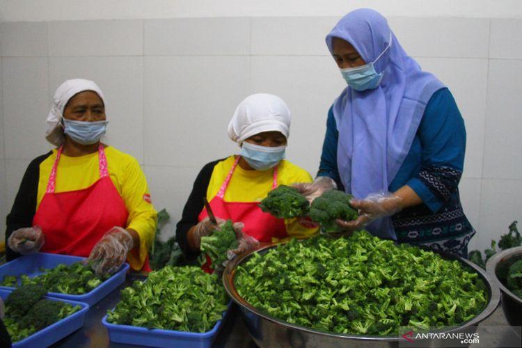 Pengusaha keripik Hari Mastutik (kanan) mengecek hasil irisan sayur brokoli yang dilakukan pekerjanya di rumah produksi keripik Momchips di Batu, Jawa Timur, Selasa (17/8/2021).
