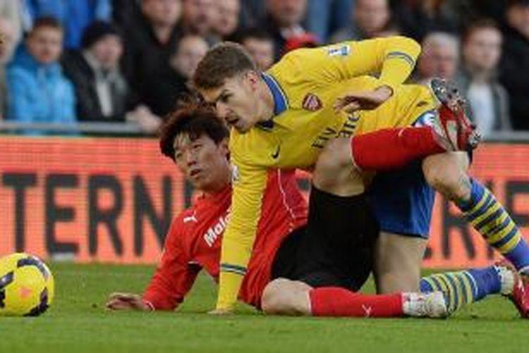 Gelandang Arsenal, Aaron Ramsey, berebut bola dengan salah satu pemain Cardiff City saat kedua tim bertemu dalam lanjutan Premier League, Sabtu (30/11/2013).