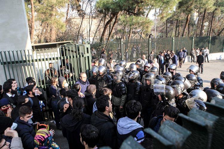 Polisi Iran berhadapan dengan mahasiswa Universitas Teheran (30/12/2017). Demo yang berawal dari memprotes kenaikan harga barang itu telah menewaskan dua warga sipil.