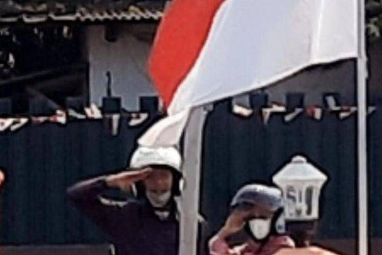 Pasutri Bayu Afirul dan Winda Nilam Sari, saat memberi penghormatan kepada Bendera Merah Putih di depan Mapolsek Driyorejo, Selasa (17/8/2021).