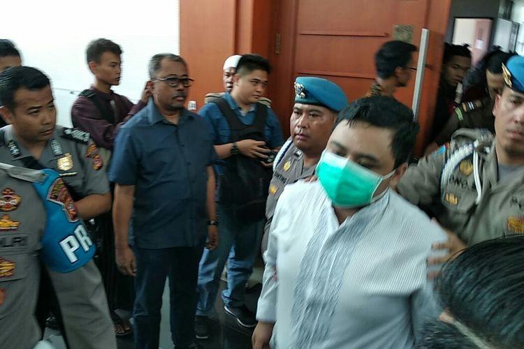 Tampak saksi korban MKU yang mengenakan masker hadir dalam pengawalan pihak kepolisian tiba di ruang sidang dugaan penganiayaan dengan terdakwa Bahar Bin Smith, Kamis (28/3/2019).