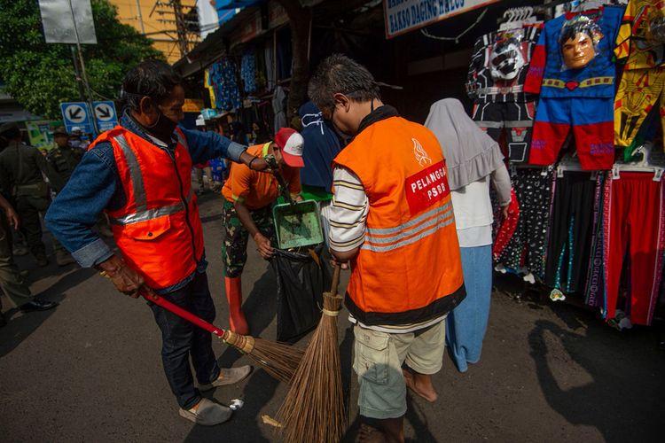 Pelanggar aturan pembatasan sosial berskala besar (PSBB) melaksanakan sanksi kerja sosial dengan menyapu sampah di Pasar Jatinegara, Jakarta, Kamis (11/6/2020). Penindakan itu untuk memberikan efek jera bagi para pelanggar agar mereka patuh terhadap kebijakan PSBB sekaligus meminimalisir potensi penyebaran COVID-19.