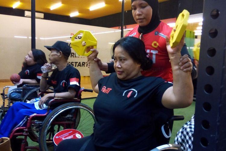 Instruktur di ReFIT Club SS72 Jalan Sepat Kebagusan Jakarta sedang membantu seorang penyandang disabilitas menggunakan dumble untuk melatih otot pada Kamis (5/12/2019).