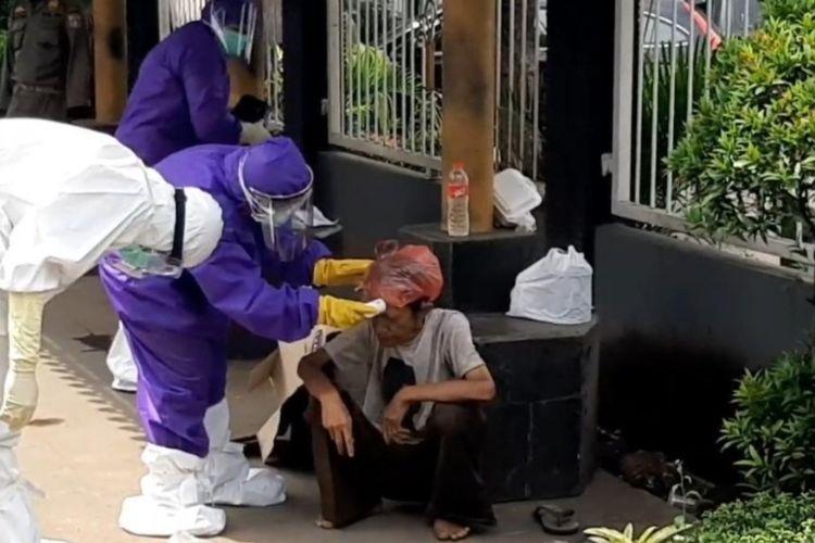 Seorang kakek jatuh pingsan di pinggir Jalan Bekasi Timur Raya, Jatinegara, Jakarta Timur, dan dievakuasi petugas medis mengenakan APD, Selasa (28/4/2020).