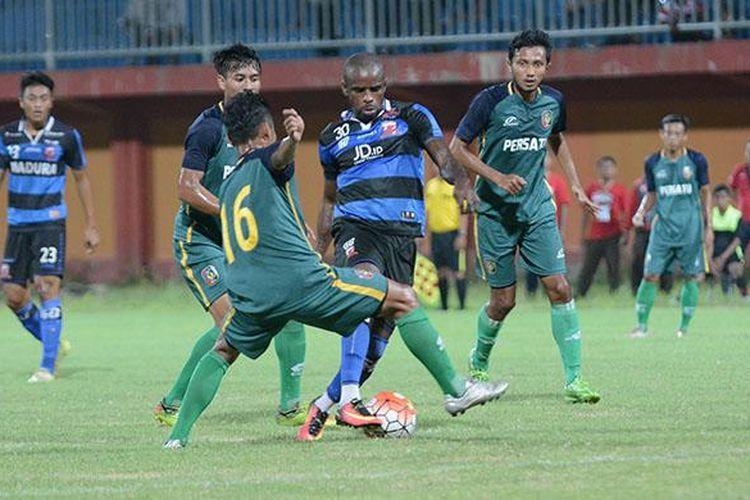 Empat pemain Persatu Tuban menghadang Greg Nwokolo saat pertandingan persahabatan di stadion Gelora Ratu Pamellingan, Ahad (5/2/2017) malam.