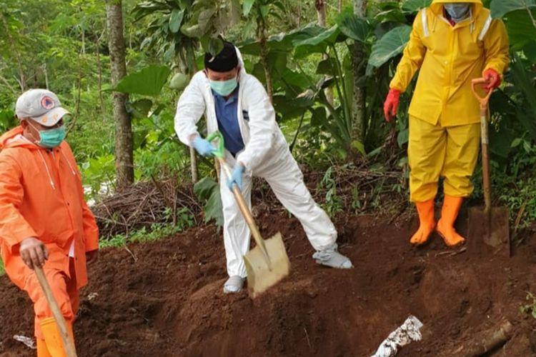 Bupati Banyumas Achmad Husein (tengah) turut membongkar makam pasien positif corona karena ditolak warga di Desa Tumiyang, Kecamatan Pekuncen, Kabupaten Banyumas, Jawa Tengah, Rabu (1/4/2020).(KOMPAS.COM/DOK BUPATI BANYUMAS)