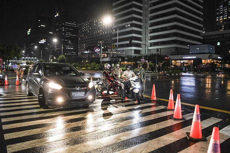 Petugas kepolisian dan Satpol PP meminta pengendara memutar arah saat diberlakukannya Car Free Night (malam bebas kendaraan)  dan Crowd Free Night (malam bebas keramaian) pada malam pergantian tahun di Jalan MH Thamrin, Jakarta (31/12/2020). Polda Metro Jaya melakukan Car Free Night dan Crowd Free Night dengan menutup sepanjang Jalan Sudirman-MH Thamrin, Jakarta pada malam pergantian tahun untuk mencegah kerumunan warga.