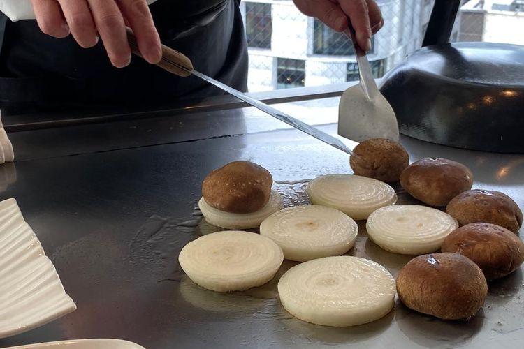 Chef memanggang bawang bombai dan jamur sebagai makanan pendamping wagyu yang tengah diolah di pelat besai panas atau dikenal sebagai teppan di Restoran Misono, Ginza, Tokyo, Jepang.
