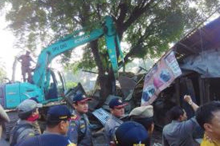 Satu unit alat berat excavator digunakan untuk menggusur kios liar yang berada di jalur hijau jalan raya Pasar Minggu pada Kamis (11/6/2015) pagi