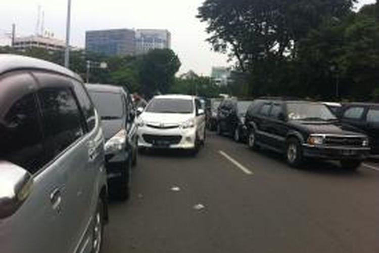 Pengunjung Monas memarkir kendaraan mereka di pinggir Jalan Medan Merdeka Selatan yang menyebabkan jalan tersebut macet, Kamis (25/12/2014).