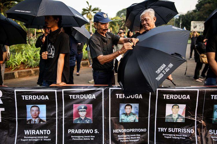Aktivis mengikuti aksi kamisan ke-588 yang digelar oleh Jaringan Solidaritas Korban untuk Keadilan di depan Istana Merdeka, Jakarta Pusat, Kamis (13/6/2019). Mereka menuntut penyelesaian kasus-kasus pelanggaran hak asasi manusia (HAM) berat yang hingga kini belum ditangani.