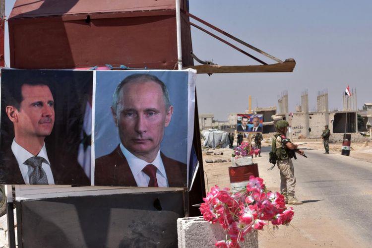 Sebuah foto memperlihatkan Presiden Suriah Bashar al-Assad (kiri) dan Presiden Rusia Vladimir Putin di persimpangan Abu al-Duhur, Provinsi Idlib, Suriah, Senin (20/8/2018). Sejak intervensi Rusia di 2015, pemerintahan Assad diklaim telah mengambil 1.400 daerah sejak pecah konflik di 2011.