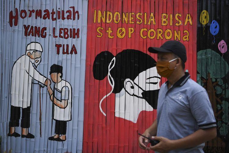 Seorang warga melintasi mural ajakan melawan penyebaran virus corona atau COVID-19 di Kalipasir, Jakarta, Jumat (10/4/2020). Selain peran pemerintah dalam penanganan COVID-19, diperlukan juga peran serta masyarakat untuk menjaga wilayah masing-masing sehingga penyebaran dapat ditekan. ANTARA FOTO/Wahyu Putro A/pras.