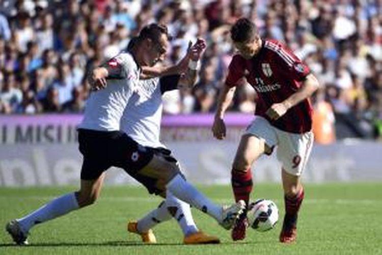 Striker AC Milan, Fernando Torres (kanan), saat berusaha melewati hadangan bek Cesena pada lanjutan Serie-A di Stadion Dino Manuzzi, Minggu (28/9/2014). Kedua tim bermain imbang 1-1 pada laga tersebut.