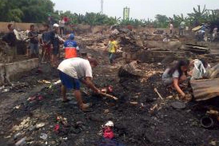 Ratusan korban kebakaran, warga kampung Bojong Kavling RT 16 RW 04 Rawa Buaya, mengais harta benda di tumpukan sisa kebakaran, Rabu (25/2/2015)